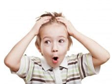 Amazed or surprised child boy hand holding hairs on head
